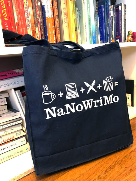 "This tote bag is navy blue and features a white print of the deconstructed NaNoWriMo logo, which appears as a coffee cup, plus sign, laptop computer, plus sign, pens crossed, plus sign, stack of books, equals sign on top of the text ""NaNoWriMo""."