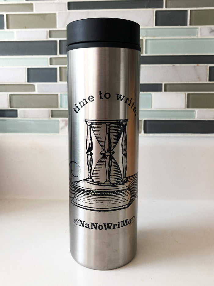 "The 2020 travel cup is a tall, steel vessel with a black press on lid. The design includes the text ""time to write"" framing an illustrated hourglass on top of a closed book with some line art flourishes around it. Beneath the illustration is the text ""NaNoWriMo"". The design and text are printed in black."