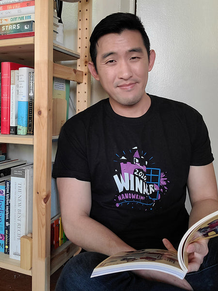 "A black T-shirt with a purple and white castle behind a blue window frame. ""2020 Winner"" is in white text and ""NaNoWriMo"" is in purple text. Leaves, stars, clouds, and a book are scattered around the castle, and a long purple rose with a blue stem runs along the bottom."