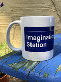 "A white mug with a dark blue wrap-around print. One side of the mug says ""Imagination Station"" in a white font that evokes classic subway station signage. The other side has four lighter blue circles with the letters N, A, N, O in their center in white and in the style of NYC subway line signage, with the word ""NaNoWriMo"" in smaller, white print below the circles. There is a thin white line going across the top of the dark blue print, above the text on both sides."
