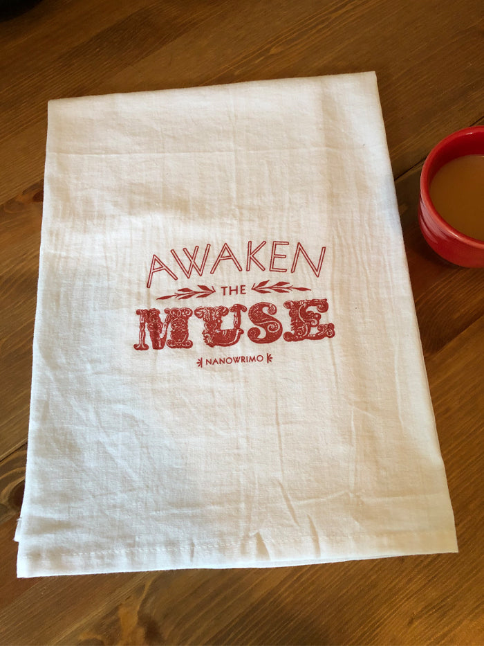 "A white cotton tea towel printed with the words ""AWAKEN THE MUSE"" in large, red text. ""Muse"" is in an extremely ornate gilded font. ""NaNoWriMo"" is printed underneath in small letters."