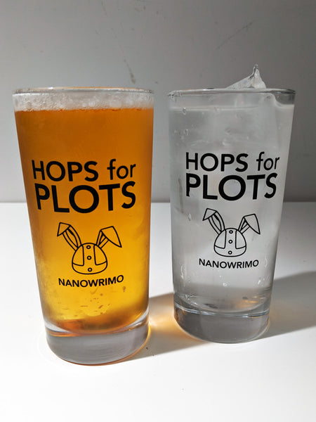 "This photo shows two of the NaNoWriMo glasses, each holding a different cold beverage. The glass is clear and features the text ""Hops for Plots"" above a Viking helmet with bunny ears. Underneath the helmet is the word ""NaNoWriMo""."