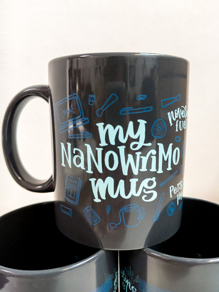 "The 2018 NaNoWriMo mug is dark gray with ""My NaNoWriMo Mug"" written on one side in light blue. The phrases noveling fuel, distilled determination, inspiration elixir, bottomless bravery, epiphany extract, and perseverance potion wrap around the mug also in light blue. Various items such as pens, pencils, papers, books, food, and beverages also wrap around the mug in dark blue."