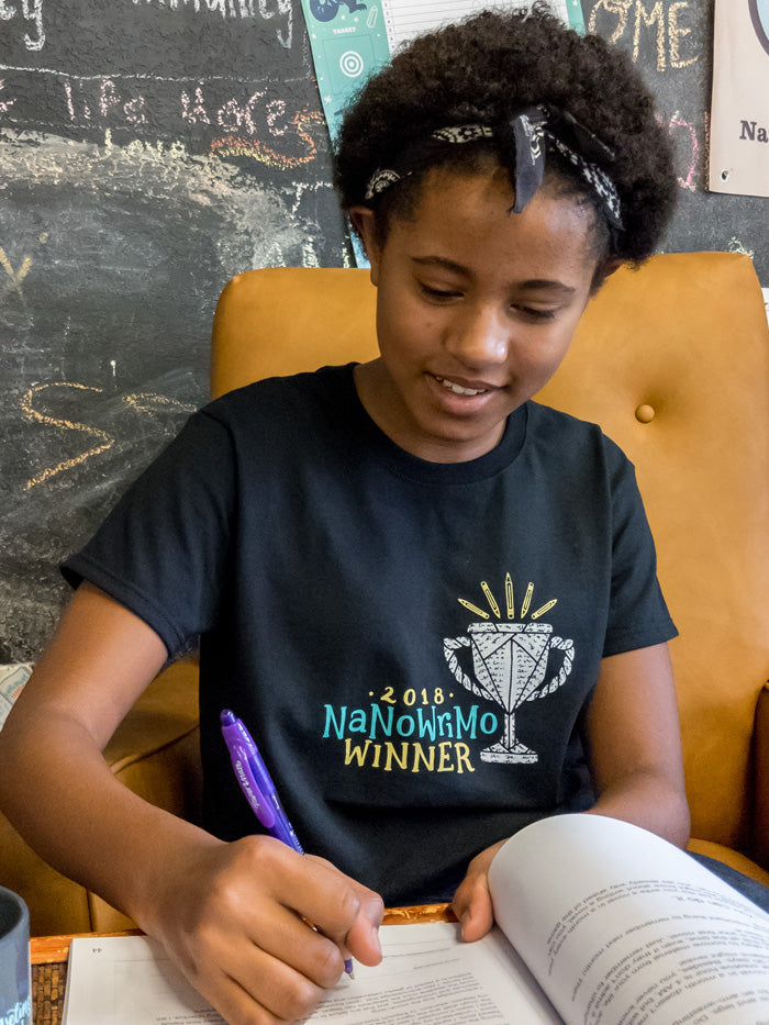 "The winner shirt is black with ""2018 NaNoWriMo winner"" in hand lettering. 2018 and winner is yellow, NaNoWriMo is turquoise. There is a winner's goblet made of twisted paper with scribbled words on it, with yellow pencils glowing like light out of the goblet."