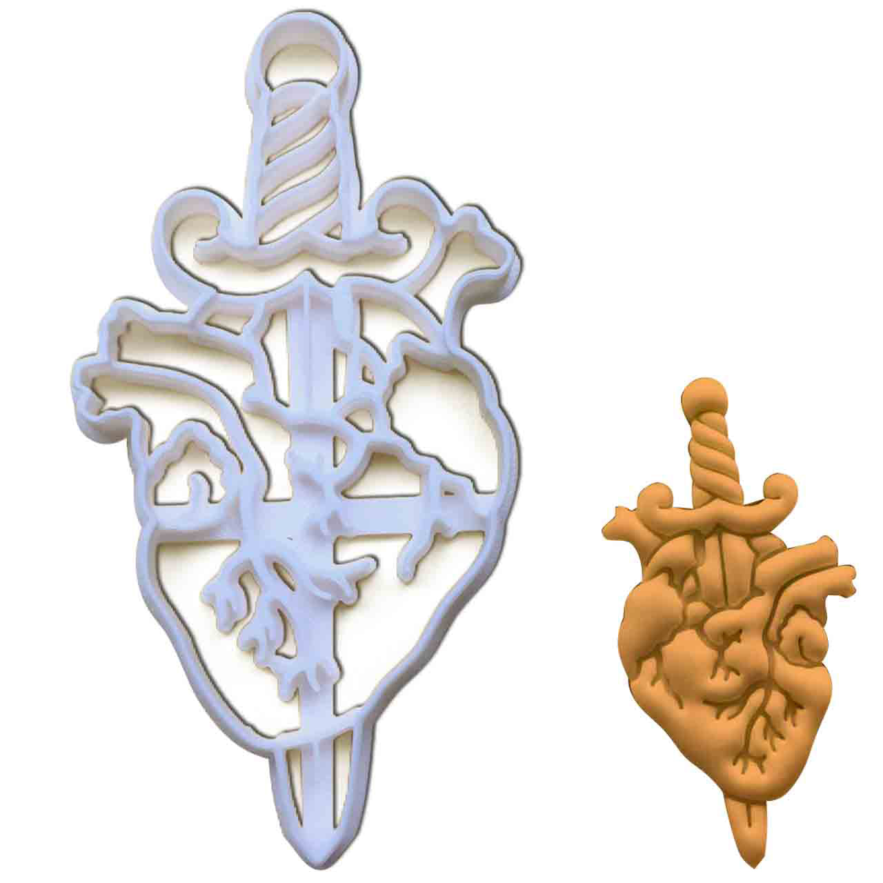dagger in anatomical heart cookie cutter pressed on white fondant