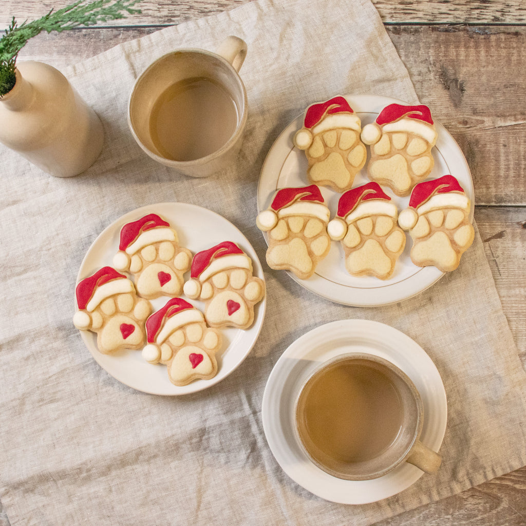 set of cute and realistic christmas dog paw with santa hat cookies