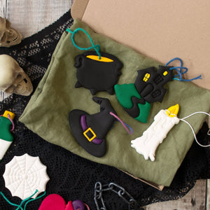 Set of 4 Witchcraft themed clay ornaments: Candle, Witch Hat, Cauldron, and Haunted House