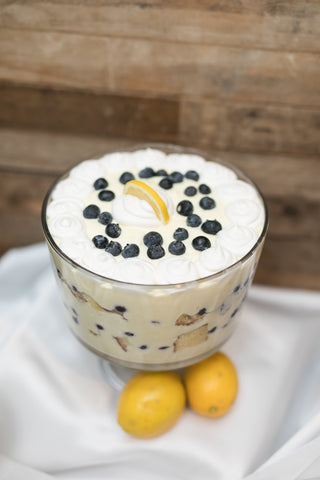 Blueberry Lemon Trifle on white table cloth with wooden background.
