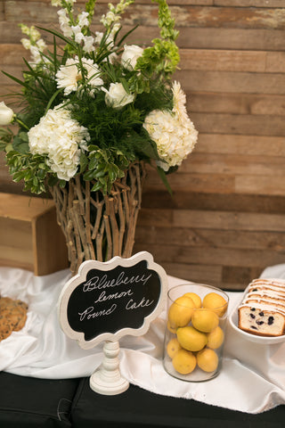 Flowers in wooden branch vase with lemons and blueberry lemon poundcake on table.