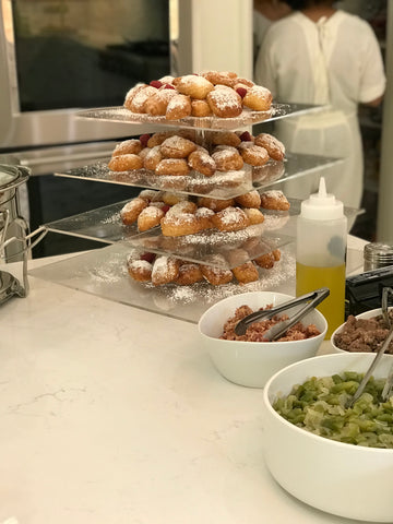 beignets on tiered acrylic display with omelet station