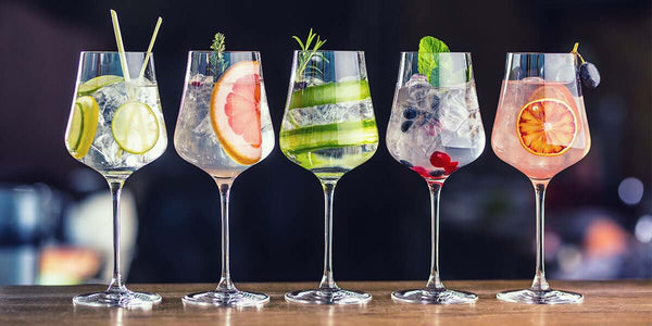 Five Elephant Gin & Snow Leopard Vodka drink mixes in wine glasses lined up with various garnishing colours.