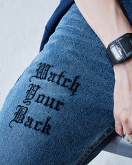 """WATCH YOUR BACK"" RUST WASHED JEANS"