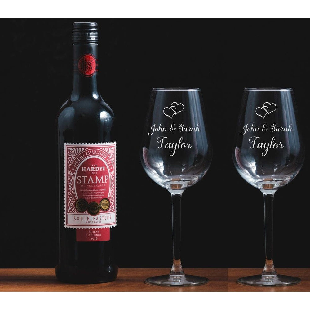 Two personalised engraved wine glasses names and entwined hearts.  The Spotted Moon Company