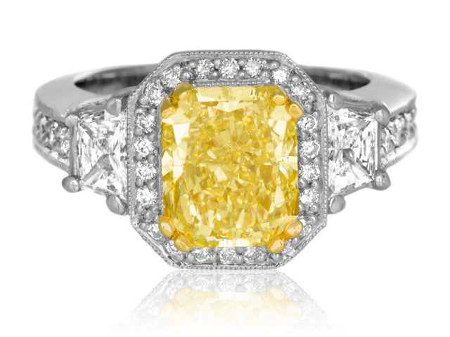 Large canary diamond ring with halo and trapezoid cut diamonds by designer Ron George.