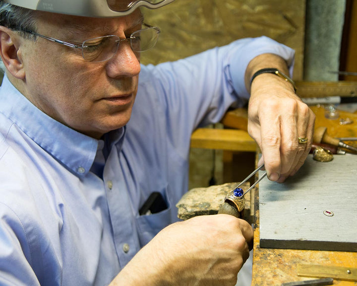Ron setting a gemstone into a Naval Academy class ring at the bench.