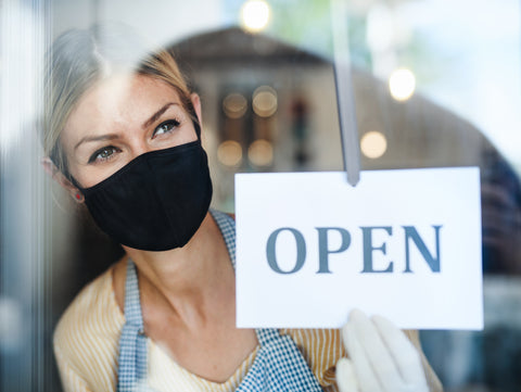 Woman with mask next to open sign
