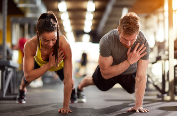 A woman and man exercising at the gym doing one-handed push-ups