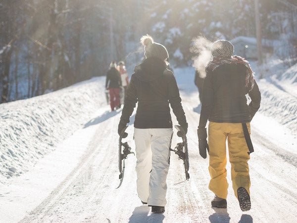 Two Snowboarders walking down a snowy path