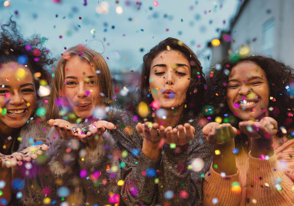group of four young women blowing glitter out of their hands
