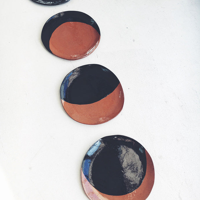 A set of four moon phase terracotta side plates