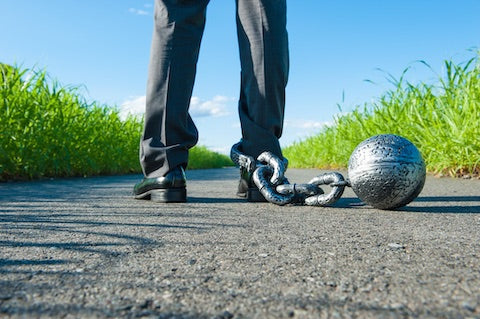 person standing with a ball and chain attached to their leg