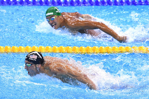 One swimmer swimming while the other is behind him and looking at him