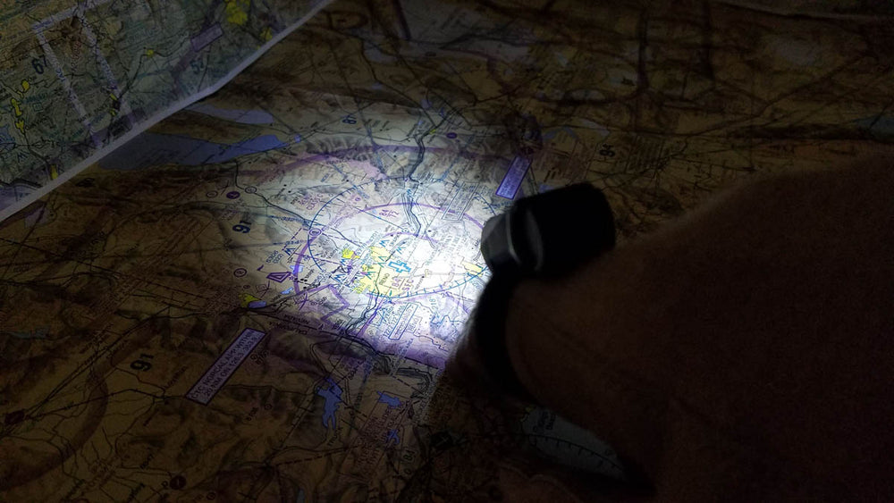 Standard White Finger Light Pro illuminating aviation chart in the dark