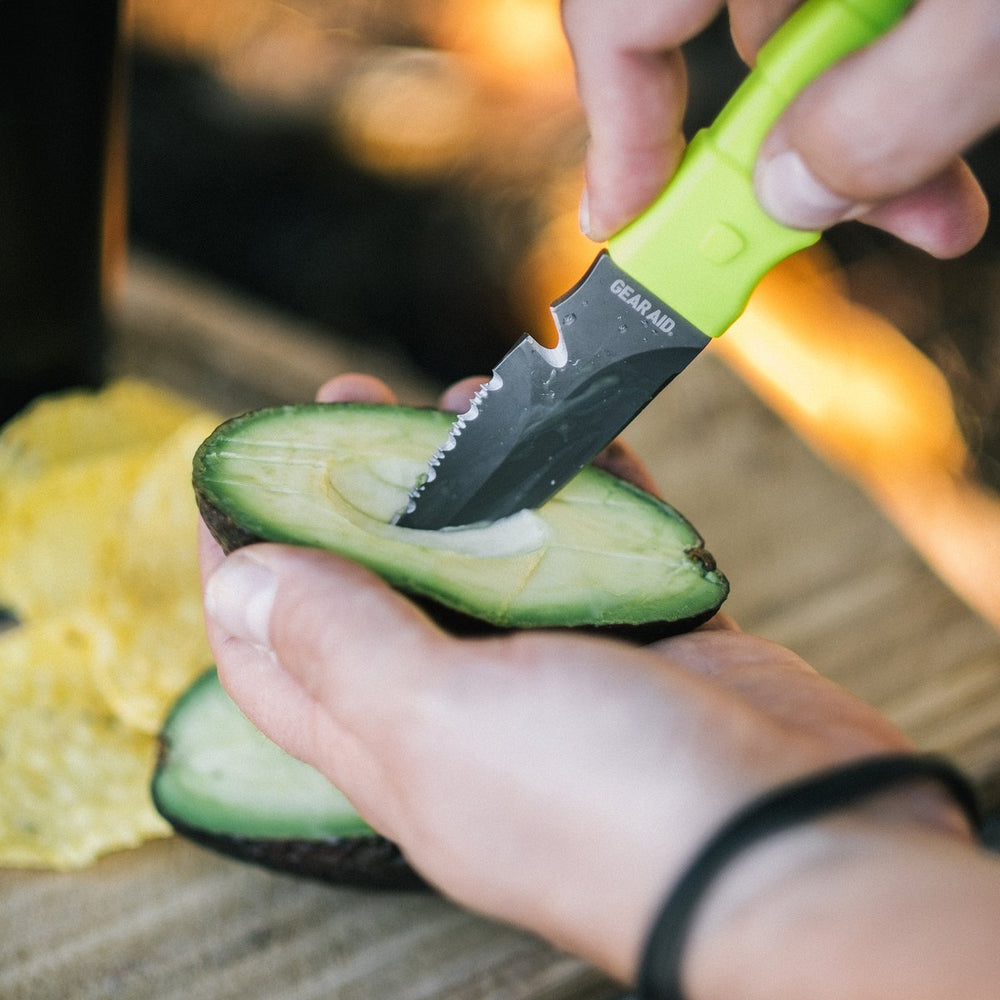 hi-vis green camp knife slicing avocado at campsite