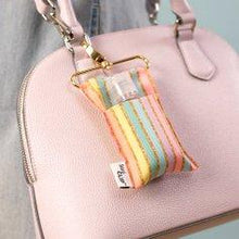 Pastel Gold Stripe SaniClip attached to the hardware of a pale pink hand bag.