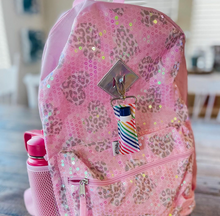 Rainbow Stripe LippyClip attached to a pink backpack