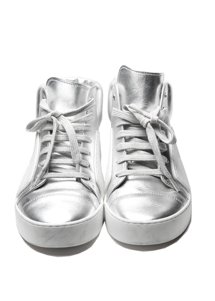 The front view of Chanel white and silver coloured sneakers