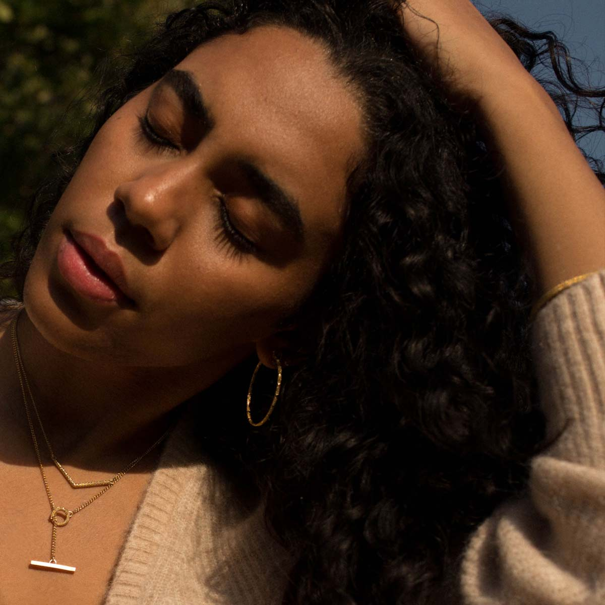 Model wearing gold t bar necklace