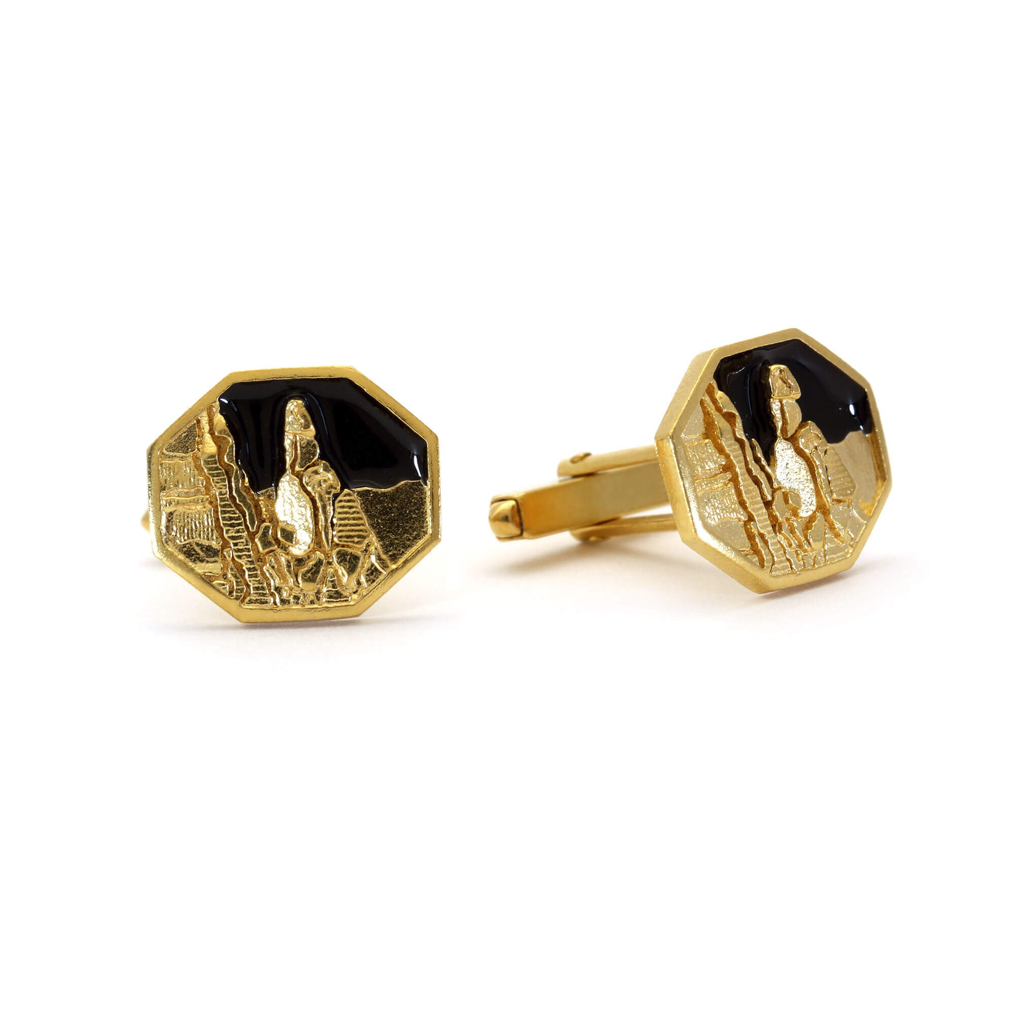 A pair of cufflinks picturing Napes Needle in gold against a black enamel sky