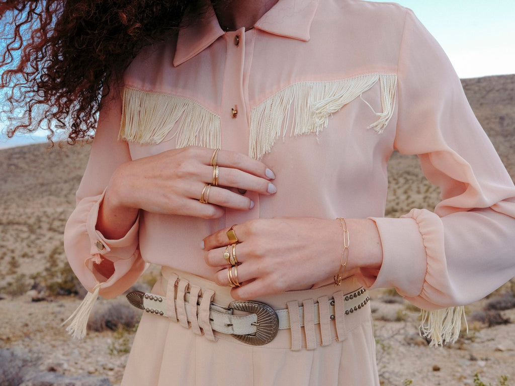woman wearing western style clothing wearing stacks of gold rings by artist erin cuff