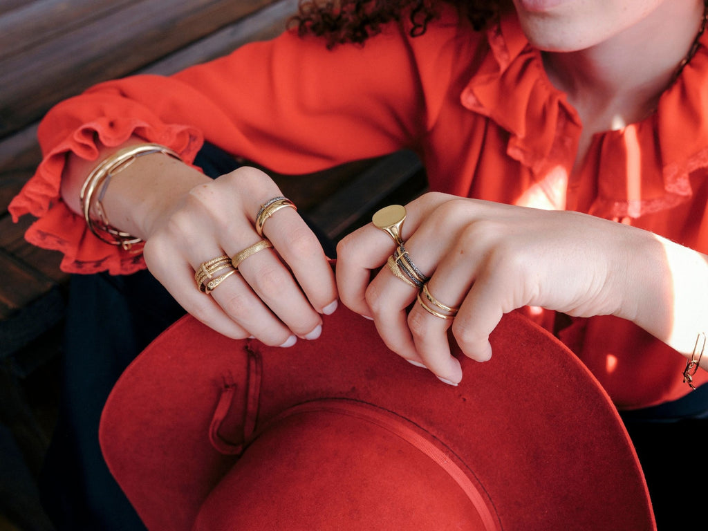 woman wearing red western style clothing and erin cuff jewelry stacked gold rings