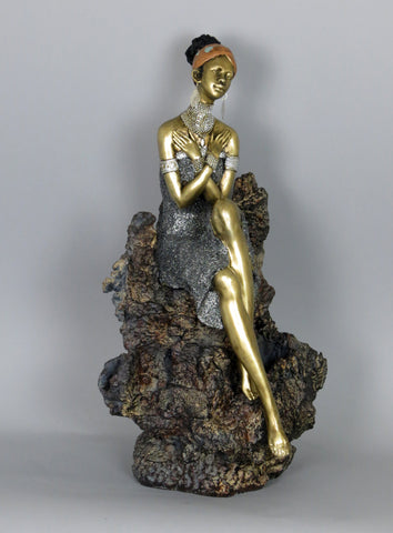 Golden African Lady Woman in Silver Dress Sat on Coral Style Rock