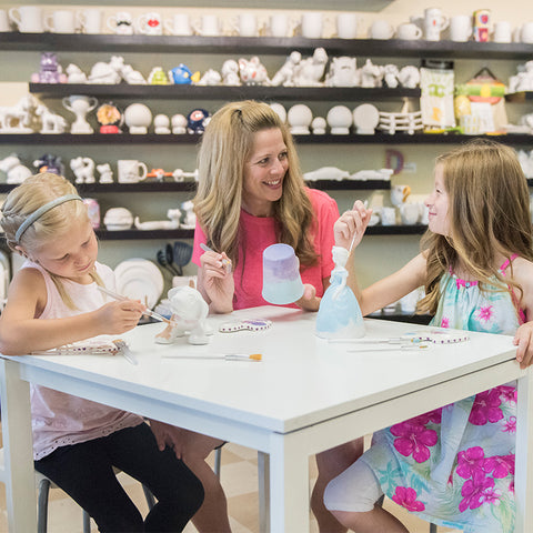 Mom and daughters having fun painting pottery and ceramics
