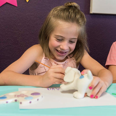 girl painting a ceramic dog at birthday party in Wisconsin Dells