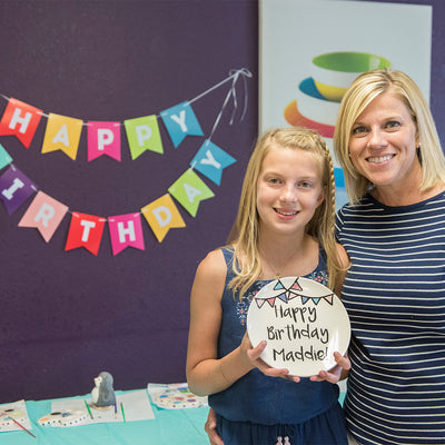 Proud mom with daughter with ceramic happy birthday plate from Polka Dot Pots in Wisconsin Dells