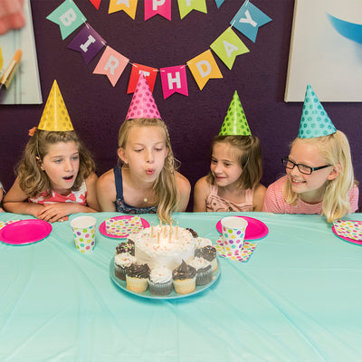 Girls blowing out birthday candles at paint your own pottery birthday party Wisconsin dells