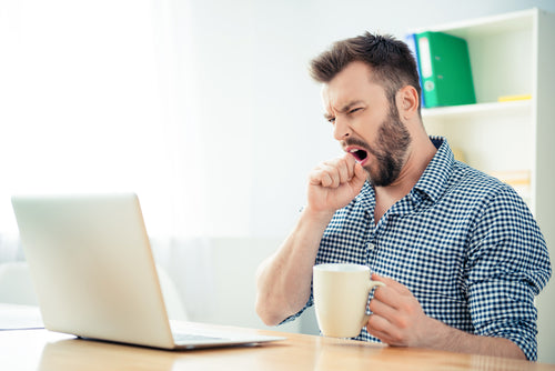 man yawning in front of laptop