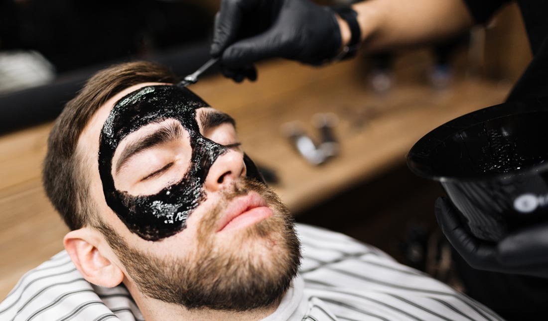charcoal mask applied to guy's face