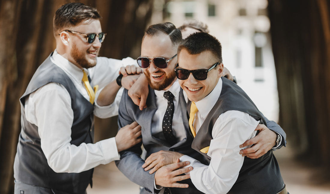 groomsmen embracing and laughing