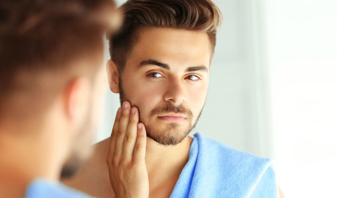guy with beard looking in mirror
