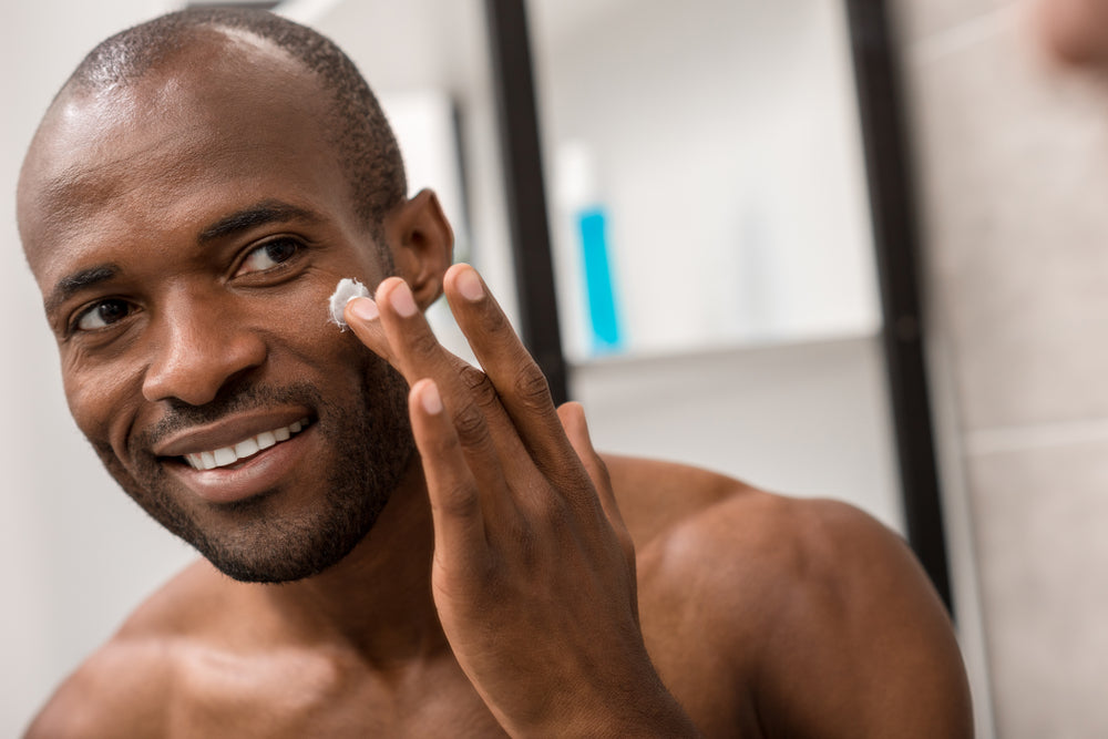 man applying facial lotion