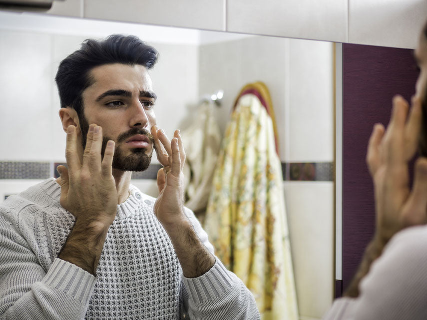 man applying facial moisturizer