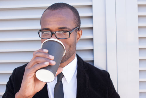 man drinking coffee outside office