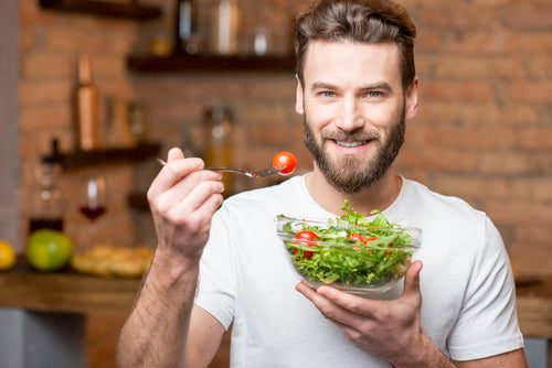 man eating salad with whole tomatoes