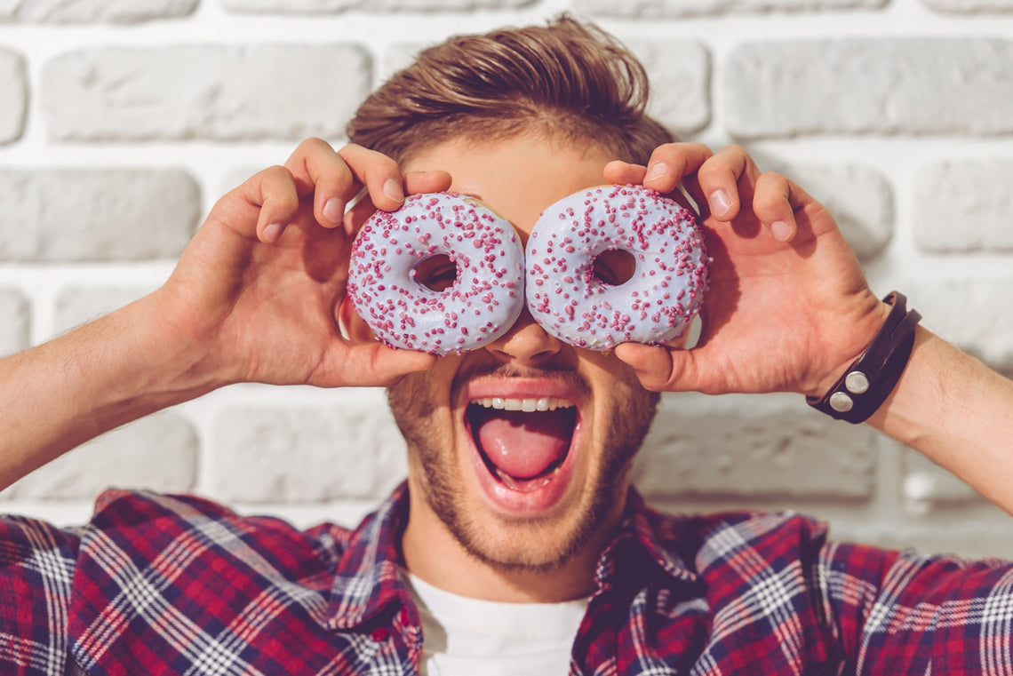 Man holding to sprinkle doughnuts over his eyes
