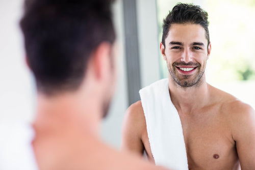 man looking through bathroom mirror